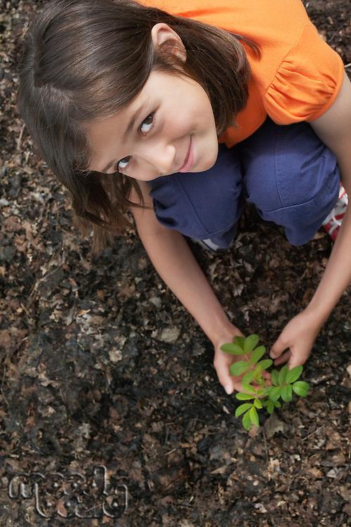 Portrait of girl (7-9) planting black locust tree