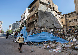 © Licensed to London News Pictures. 16/07/2014. Gaza.   Children walk past the remains of a home destroyed in an Israeli air strike in Gaza city.  According to a local resident the building was owned by a mechanic.  Photo credit : Alison Baskerville/LNP