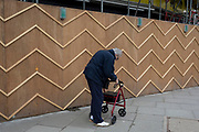 An elderly pensioner struggles to walk using a four-wheeled rollator mobility aid past the zigzag battens of a construction hoarding at Notting Hill, on 13th March 2018, in London, England.