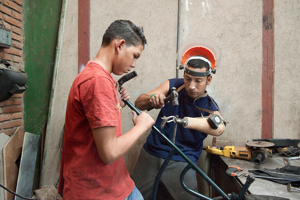 José and Alejandro work on a wheelchair at the PLUSAA workshop in León, Nicaragua.