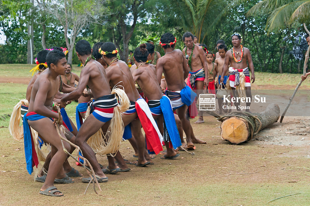 Yapese men in traditional clothing carrying log, Yap Island, Federated States of Micronesia