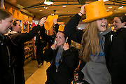 03/19/2014- Milwaukee, Wisc. - Kelsey Morehead, A15, and her teammates try on Wisconsin cheese heads at Mitchell International Airport after arriving in Milwaukee for the NCAA Division III Women's Final Four on Mar. 19, 2014. (Kelvin Ma/Tufts University)