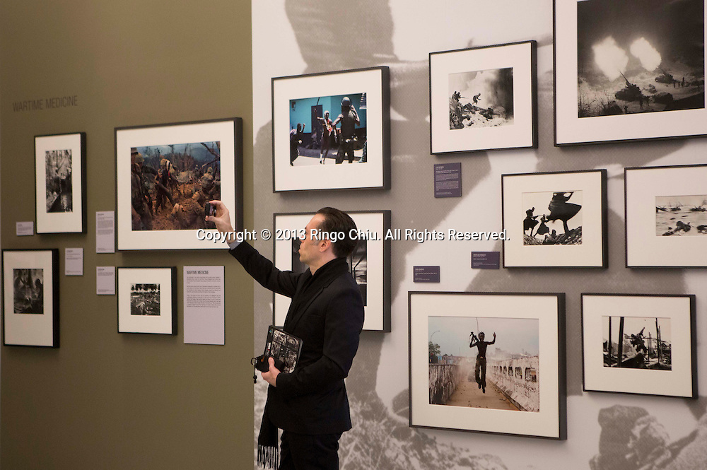 A man takes pictures in the Annenberg Space for Photography gallery Wednesday in Los Angeles, California. The Gallery will present the exhibit, ``War/Photography,'' featuring ``images of armed conflict and its aftermath.'' from March 23 to June 2. The exhibit includes more than 170 print images from 1887 through the present day. (Photo by Ringo Chiu/PHOTOFORMULA.com).