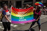 "New York, NY - 25 June 2017. New York City Heritage of Pride March filled Fifth Avenue for hours with groups from the LGBT community and it's supporters. Marchers carry a banner reading ""Make America gay again,"" a dig at President Trump's campaign slogan."