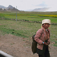 A Tibetan girl walking in the countryside warily passes Western visitors. 8/9/05.