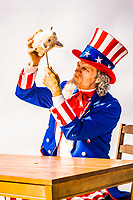 An Uncle Sam character holding up a piggy bank and attempting to pry every last penny out of it. Conceptual shot of breaking the bank, every last penny, raiding the coffers, deficits, the US Treasury.