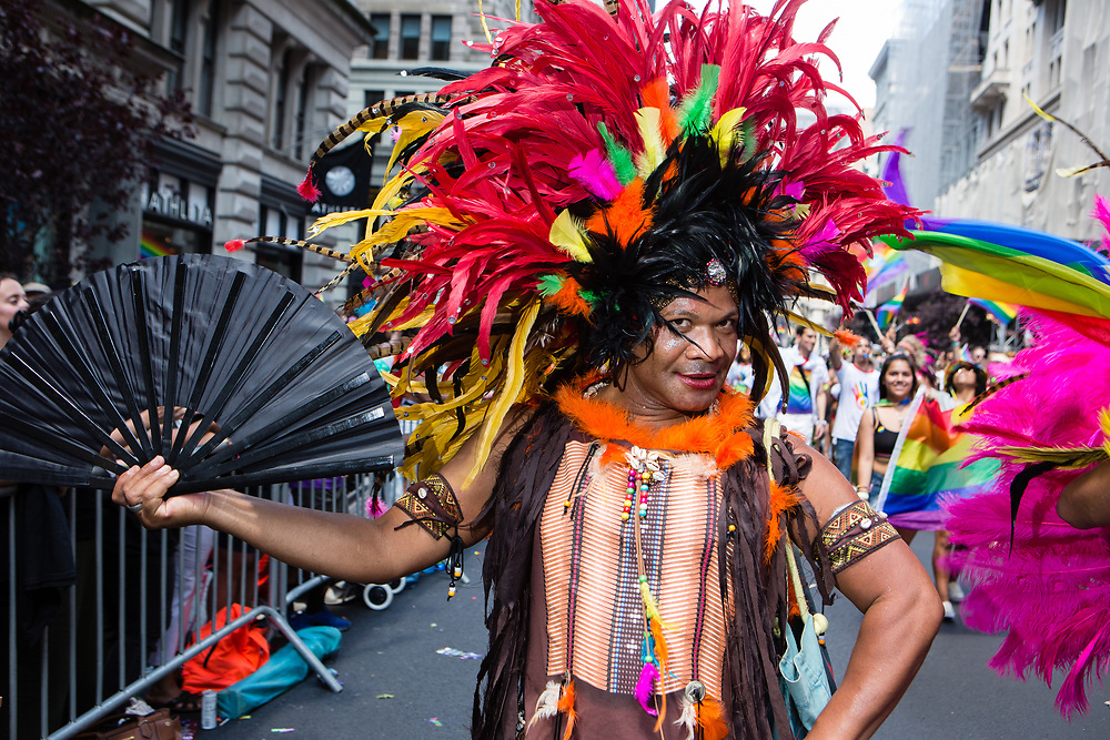 New York, NY - 30 June 2019. The New York City Heritage of Pride March filled Fifth Avenue for hours with participants from the LGBTQ community and it's supporters. A man wears a brightly coloredf feathered headdress.