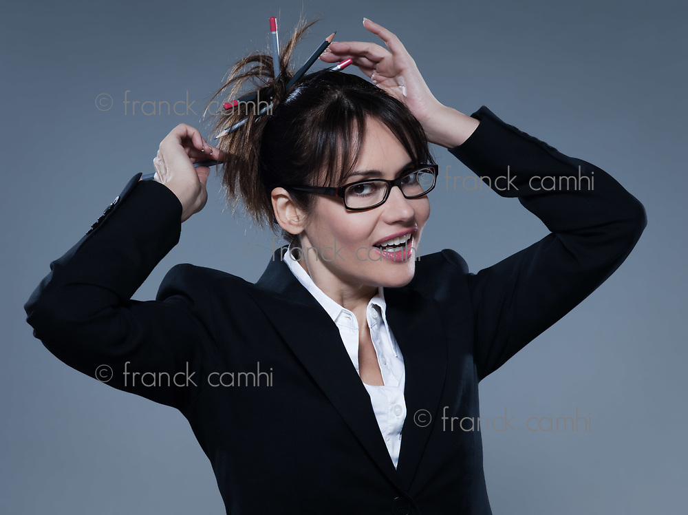beautiful business woman on isolated bacground doing bunhair with pencil