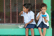 Two girls sit together as they eat their lunch at the primary school in the town of Coyolito, Honduras on Wednesday April 24, 2013.