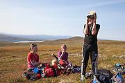 Magnus Kurås speider i kikkert mens Anne Brynhildsvoll (t.v.), Ellinor Marie Bransfjell og Mari Tamnes tar en pust i bakken.