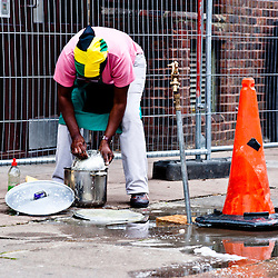 London, UK - 27 August 2012: a woman wearing a jamaican flag washes dishes on the streets during the Notting Hill Carnival.
