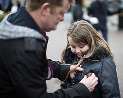 © Licensed to London News Pictures . 28/01/2017 . Stoke-on-Trent , UK . A party supporter places a UKIP badge on his daughter's jacket . UKIP formally launch their campaign in the by-election in the constituency of Stoke-on-Trent Central , at their new campaign shop at 1 Piccadilly in Stoke , with candidate - and party leader - Paul Nuttall . The seat was vacated when Tristram Hunt resigned . Photo credit : Joel Goodman/LNP