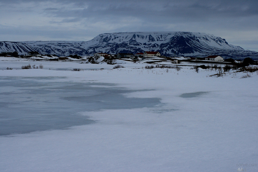 Dusk falls over a village on the southern shore of Lake Myvatn, still frozen at the end of March at the edges, in Northern Iceland