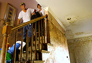 Cheryl Jenning, right, and her father George carry a suitcase of baby clothes from the second floor while trying to salvage some belongings from Jenning's home in Chalmette, La. Jenning was brought to tears upon viewing the damage to her home for the first time Monday. The house's first floor was filled with half a foot of mud and mold covered the walls, but the second floor was left undamaged by the flooding caused by Hurricane Katrina.
