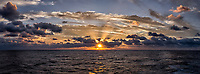 Sunrise, sunburst, crepuscular rays, and clouds over the Pacific Ocean from the aft deck of the MV World Odyssey. Composite of three vertical images taken with a Fuji X-T1 camera and 23 mm f/1.4 lens (ISO 200, 23 mm, f/16, 1/60 sec). Raw images processed with Capture One Pro and AutoPano Gig Pro.