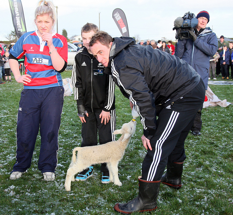 """Jimmy Cowan feeds a lamb at the """"All Blacks Coming to a Town Near You"""" visit, Midlands Rugby Ground, Winton, New Zealand, Friday, September 02, 2011. Credit:SNPA / Dianne Manson."""