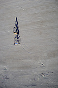 Vertical aerial view of two bikers riding on the beach, early morning, long shadows