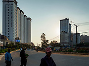 "13 FEBRUARY 2019 - SIHANOUKVILLE, CAMBODIA:  Cambodian laborers walk past the Xihu Resort Hotel in Sihanoukville. There are about 80 Chinese casinos and resort hotels open in Sihanoukville and dozens more under construction. The casinos are changing the city, once a sleepy port on Southeast Asia's ""backpacker trail"" into a booming city. The change is coming with a cost though. Many Cambodian residents of Sihanoukville  have lost their homes to make way for the casinos and the jobs are going to Chinese workers, brought in to build casinos and work in the casinos.      PHOTO BY JACK KURTZ"