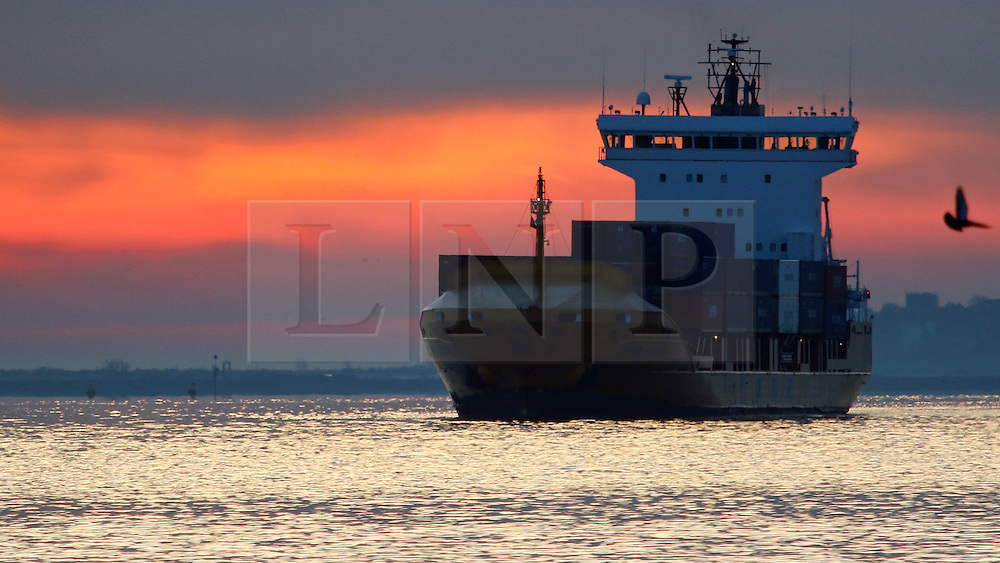 © Licensed to London News Pictures. 13/04/2016. Sunrise seen this morning over the Thames at Gravesend in Kent. Container ship OPDR LISBOA seen heading towards Tilbury. Credit : Rob Powell/LNP