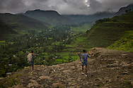 Two young men near the end of a long walk to their village in the Ethiopian Highlands.  Good roads are far and few between, and motor transport still rare between towns and mountain villages.  Ethiopians here still walk long distances to towns, and depend on their farms and animals for subsistences.  This makes them far more dependent on the variable seasonal rains, unusually heavy this year, to provide for food for their families.  Ethiopian Highlands.