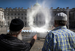 © Licensed to London News Pictures. 25/06/2018. London, UK. Visitors to Somerset House view 'HALO' an art installation that uses 99 mirrors to track the sun and draw a circle of light in a mist of water. Created by Seoul-based experimental art studio Kimchi and Chips (founded by Mimi Son and Elliot Woods) the display runs until June 27th, 2018. Sunny weather has brought high temperatures to most of the UK. Photo credit: Peter Macdiarmid/LNP