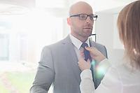 Woman adjusting businessman's tie at home
