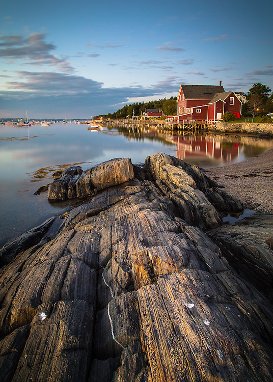 One of the most captivating views of Orr's Island is from the rocks off the boat launch at Prince's Point.<br /> <br /> From here you can look back up the shoreline of Harpswell Sound. The iconic structure of the old Prince building, one of the centers of the codfish trade in the 1800's, now the Salt Cod Cafe, rests against the water, its red paint making it an even better subject for photographers, painters, and other artists who frequent the area.<br /> <br /> I captured this image after the sun set, casting a warm glow on the scene. Thanks for looking.