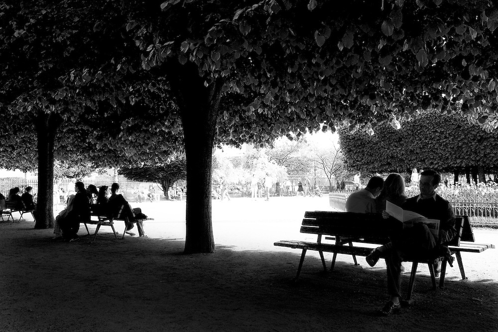 "Silhouettes of people relaxing and enjoying the shade sitting on park benches at the tree lined flower garden behind Notre Dame ""Our Lady"" or Notre Dame de Bonne-Nouvelle, ""our lady of good news"", Paris, France next to the River Siene."