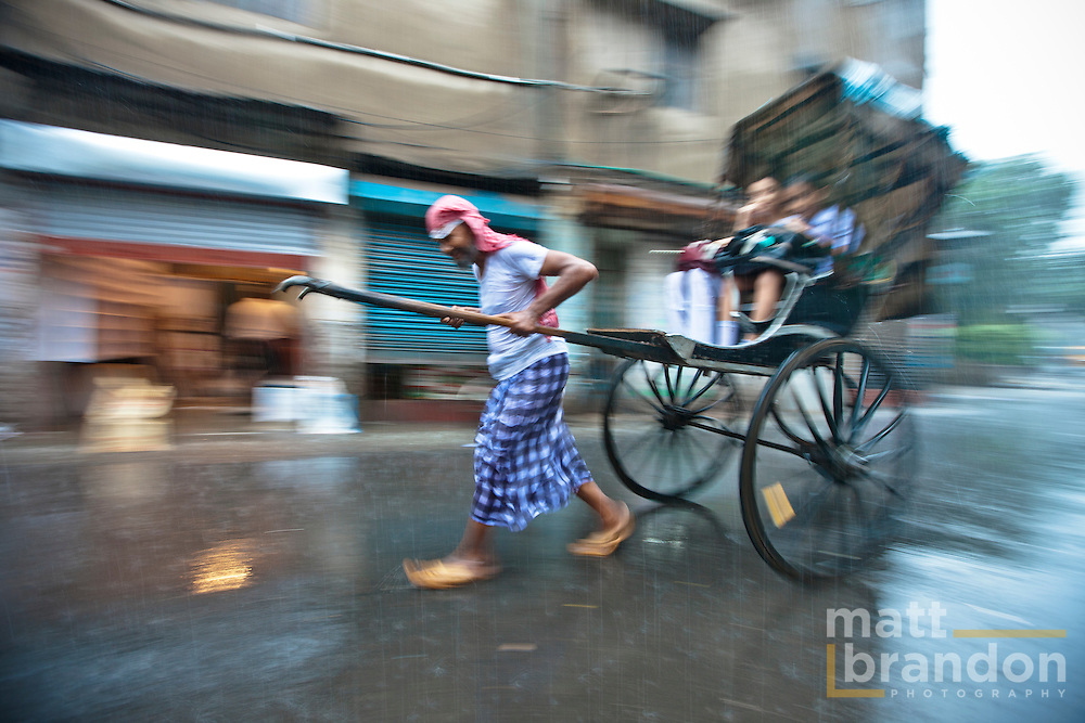 The weather makes no difference. Even in the monsoon the rickshaw puller continues to ply the streets of Kolkata.
