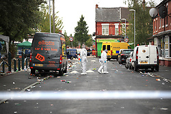 Forensics officers at the scene in Claremont Road, Moss Side, Manchester, where ten people, including two children were taken to hospital after reports of gunshots at a street party.