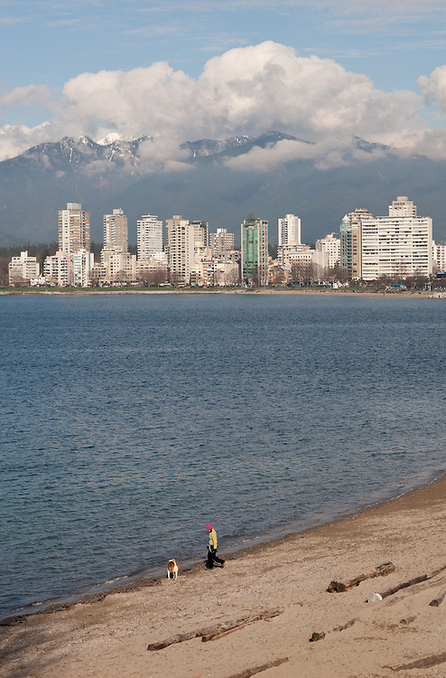 A sunny view looking over the Burrard Inlet in Kitsilano, Vancouver. A popular area for dog walkers and joggers eager for excercise. The city of vancouver is in the background followed by a backdrop of mountains.