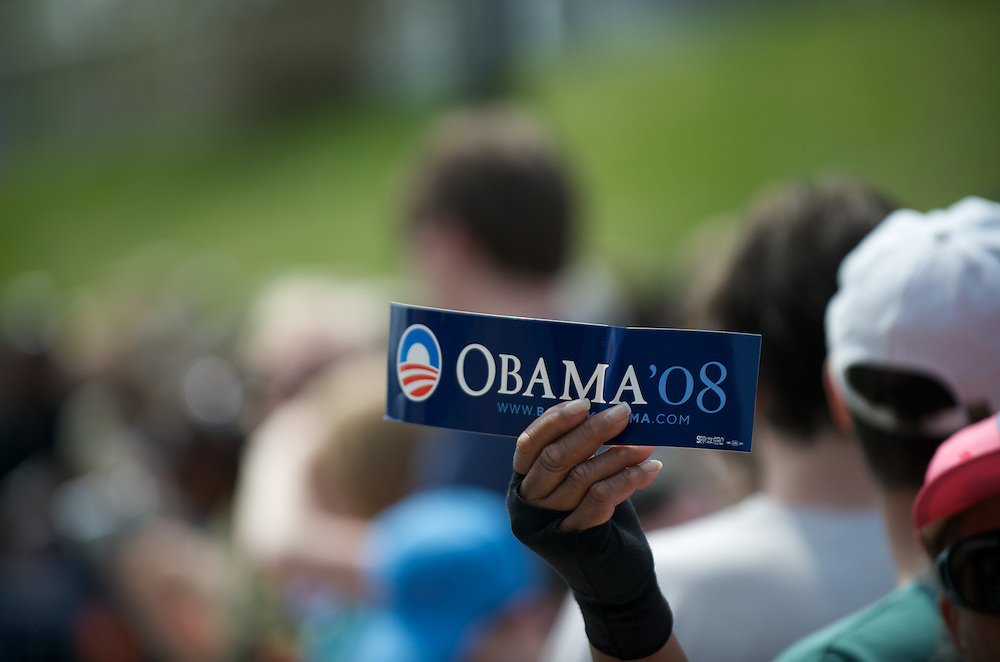 An Obama supporter holds a bumper sticker in anticipation of the senator's arrival at a Saturday morning rally.