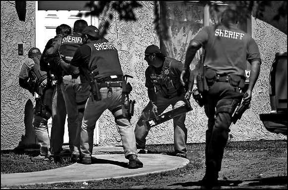 Michael Stenerson / Staff Photographer.Authorities prepare to break in the door and serve a search warrant a residence in Adelanto on Thursday. Large amounts of methamphetamine and cash were found after searching the residence.
