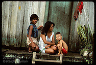 Mother sits with son and daughter on front porch of their shack in Eirunepe slum, Amazonas state Brazil