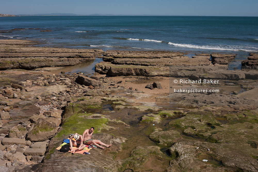A man and woman sit on rocks rubbing in sunblock with Atlantic waves coming in the background, on 12th July 2016, at Estoril, near Lisbon, Portugal. Cascais is a coastal town and a municipality in Portugal, 30 kilometres (19 miles) west of Lisbon. The former fishing village gained fame as a resort for Portugal's royal family in the late 19th century and early 20th century. Nowadays, it is a popular vacation spot for both Portuguese and foreign tourists and located on the Estoril Coast also known as the Portuguese Riviera. (Photo by Richard Baker / In Pictures via Getty Images)