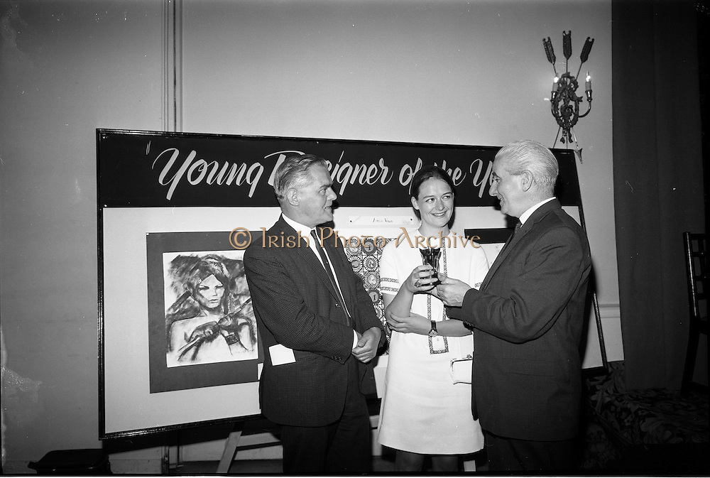 """28/06/1967<br /> 06/28/1967<br /> 28 June 1967<br /> Presentation of prizes at Navan Carpets """"Young Designer of the Year"""" reception in the Royal Hibernian Hotel, Dublin. Image shows Ms Linda Willis (20) a College of Art student from Dun Laoghaire, who was named Ireland's """"Young Designer of the Year"""". Linda, who was born in Venice, received her prize with the other award winners at the reception. Left -right are: Mr. Allan Mallinson, Managing Director, Navan Carpets Ltd.; Ms Willis and  Mr. James White, Director National Gallery of Ireland who is presenting Ms Willis with the trophy."""
