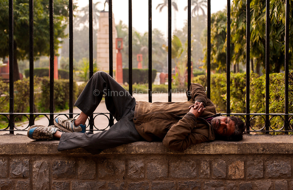 19th February 2014,New Delhi. A man sleeps on a wall in Old Delhi, India on the 19th February 2014<br /> <br /> Sleeping in the outdoors is common in Asia due to a warmer climate and the fact that personal privacy for sleep is not so culturally ingrained as it is in the West. New Delhi (where most of these images were taken) is a harsh city both in climate and environment and for those working long hours, often in hard manual labour, sleep and rest is something fallen into when exhaustion overwhelms, no matter the place or circumstance. Then there are the homeless, in Delhi figures for them from Government and NGO sources vary wildly from 25,000 to more than 10 times that. Others public sleepers may simply be travellers having a siesta along the way.<br />  <br /> <br /> PHOTOGRAPH BY AND COPYRIGHT OF SIMON DE TREY-WHITE, photographer in Delhi<br /> <br /> + 91 98103 99809<br /> email: simon@simondetreywhite.com