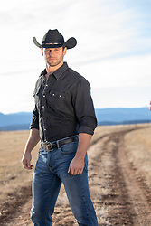 hot cowboy standing on a dirt road on a ranch
