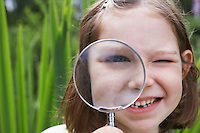 Portrait of girl (7-9) looking through magnifying glass