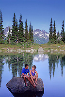 A couple relaxes by Harmony Lake, Whistler mountain on a  sunny summer evening.