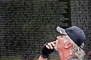 A visitor to the Vietnam Veterans Memorial scans the names of the fallen etched in the monument during a visit on Sunday May 24, 2009.