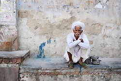 A man taking a break after a long day outside a city wall. Photo taken while traveling in Rajasthan, India, with Steve McCurry.