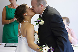 Bride who has cerebral palsy, kissing groom at wedding ceremony.