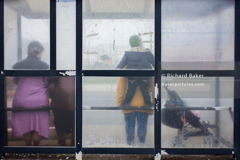 Locals await the next bus in a public transport bus shelter, St. Leonard's-on-Sea.