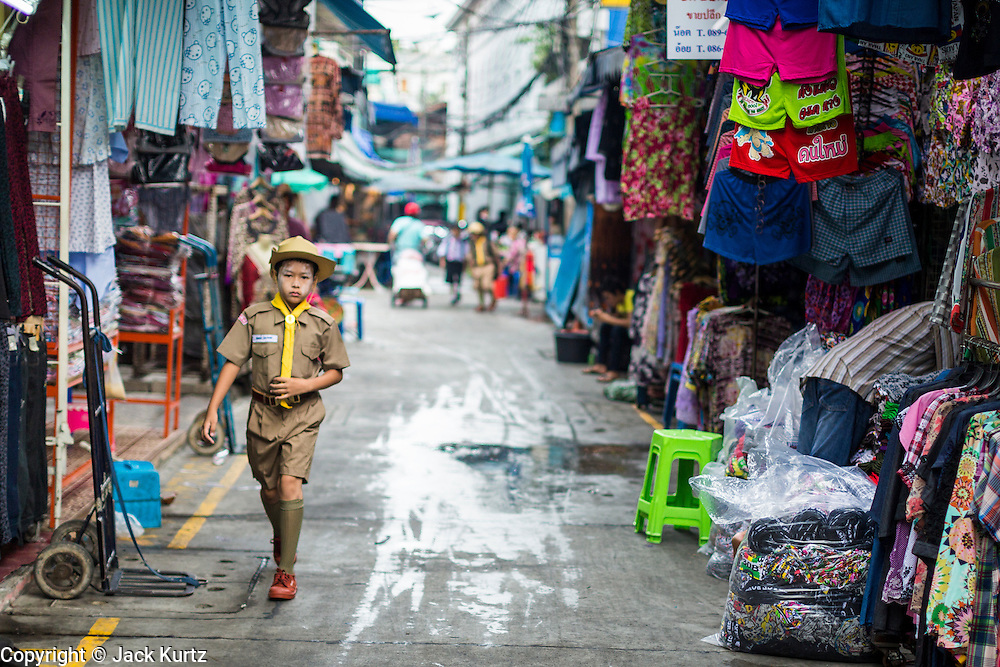 06 JUNE 2013 - BANGKOK, THAILAND: A Boy Scout walks from his home to his school through Bobae Market in Bangkok. Bobae Market is a 30 year old famous for fashion wholesale and is now very popular with exporters from around the world. Bobae Tower is next to the market and  advertises itself as having 1,300 stalls under one roof and claims to be the largest garment wholesale center in Thailand.       PHOTO BY JACK KURTZ