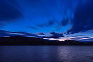Venus as the lone &ldquo;evening star&rdquo; shining in the twilight sky with clouds moving out of the northwest over the Waterton River, at Waterton Lakes National Park. This was June 14, 2018.<br /> <br /> This is a stack of 100 images for the sky and clouds, blended with the Advanced Stacker Plus actions ultrastreak mode normally used to produce star trails, but here used to produce cloud trails, to produce a blurred motion effect showing the motion of the clouds at this windy location. In addition, I applied a radial &ldquo;zoom&rdquo; blur to further smooth the images and motion effect. Venus is added from a single exposure from the end of the sequence. The ground and water foreground are from a mean-stacked blend of 8 exposures to smooth noise and the rippled water from the high wind this night.<br /> <br /> All with the Sigma 20mm lens and Nikon D750 on Auto Exposure for a time-lapse with shifting shutter speeds as the sky darkened.