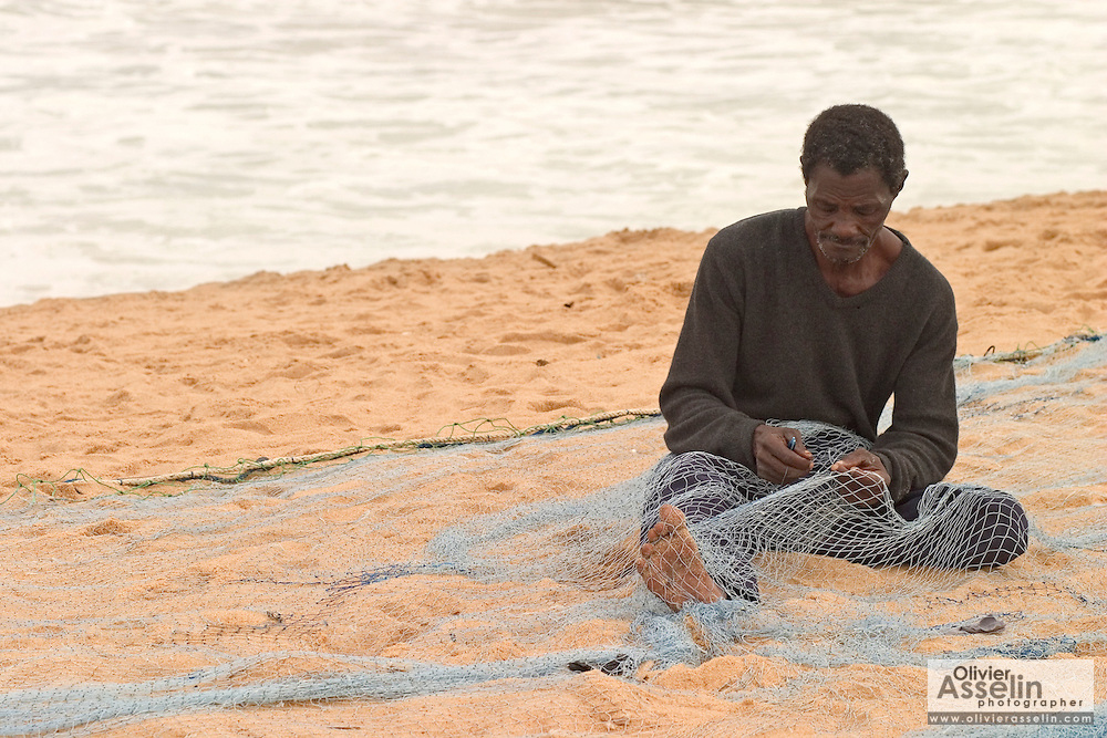 Fisherman repairing fishing nets on the beach at Aflao, Volta region, Eastern Ghana.