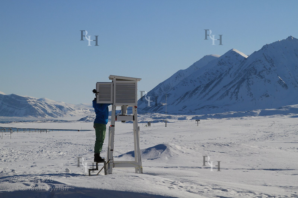 Woman checks weather station box in April at the international science village of Ny-Alesund on Spitsbergen island in Kongsfjorden; Svalbard, Norway.