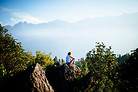 A young traveler sits and overlooks a mountainous landscape in Sapa, Vietnam.
