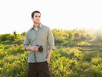 Portrait of mid adult man in fields holding binoculars